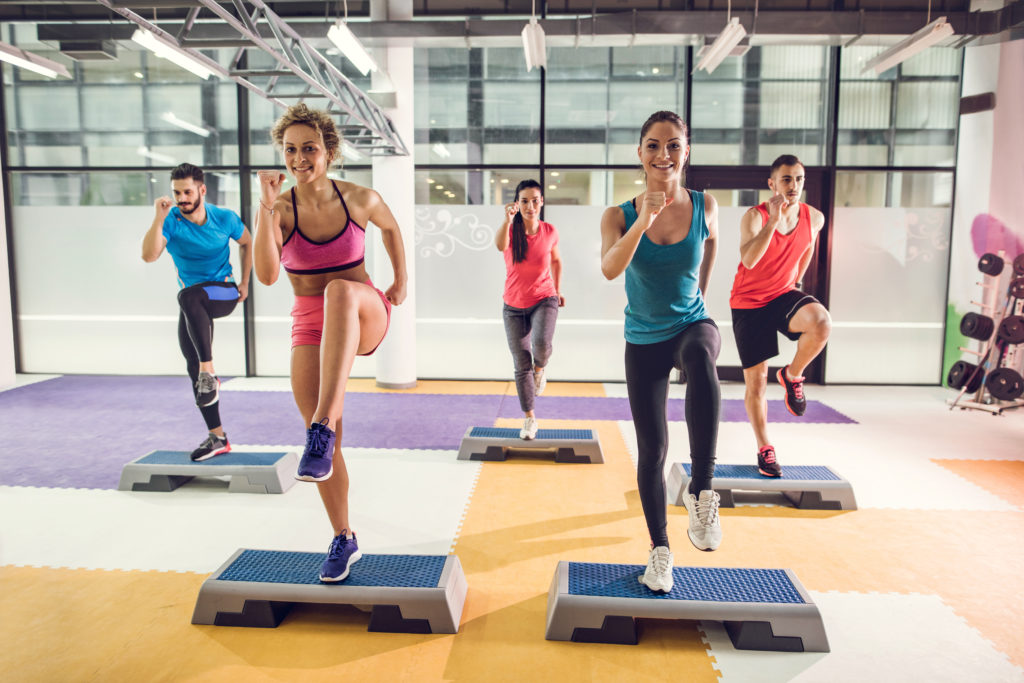 Group of athletic people exercising step aerobics in a gym.