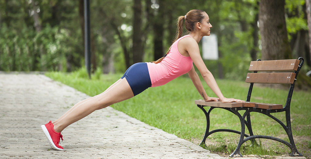 Young woman doing pushups on bench in the park
