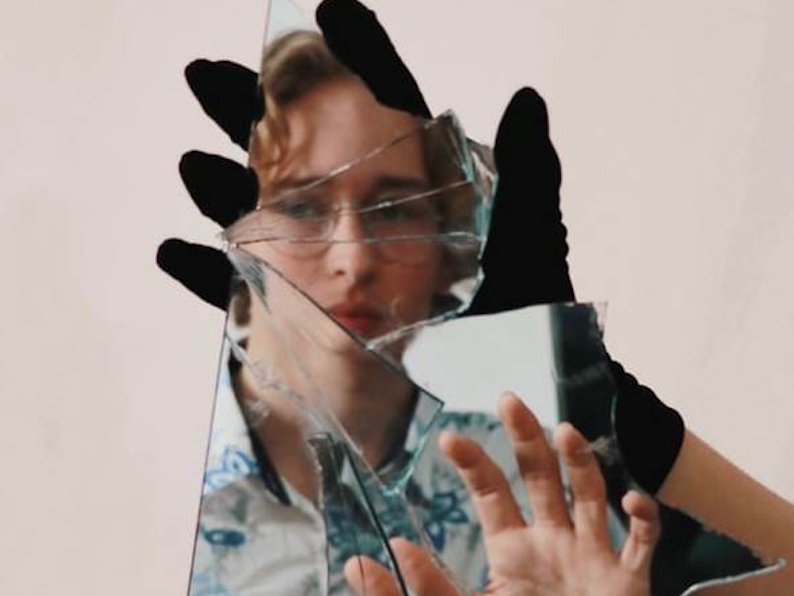 broken glass looking at reflection in mirror body image article