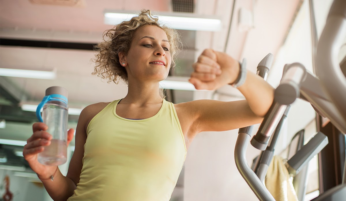 Blonde woman in yellow tanktop working out at fitness center