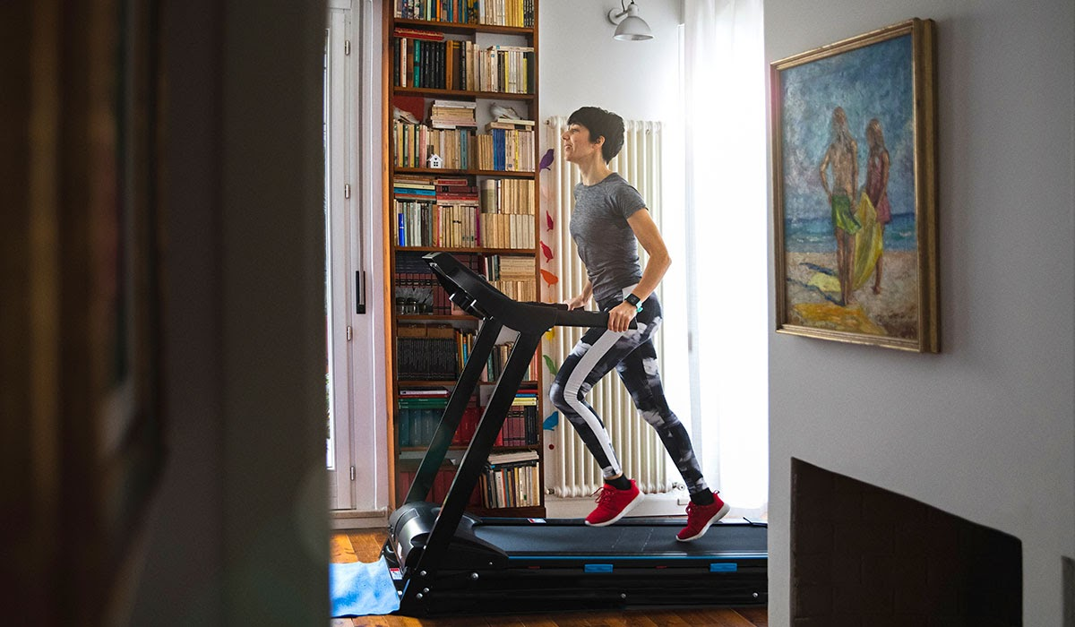 Woman working out at home on treadmill cardio machine