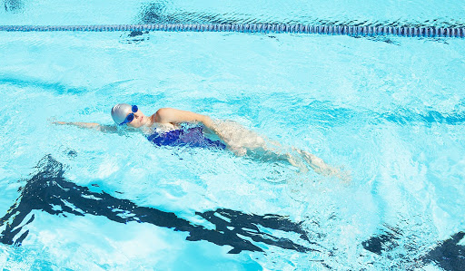 Woman in blue bathing suit, and grey swim cap swimming in a pool