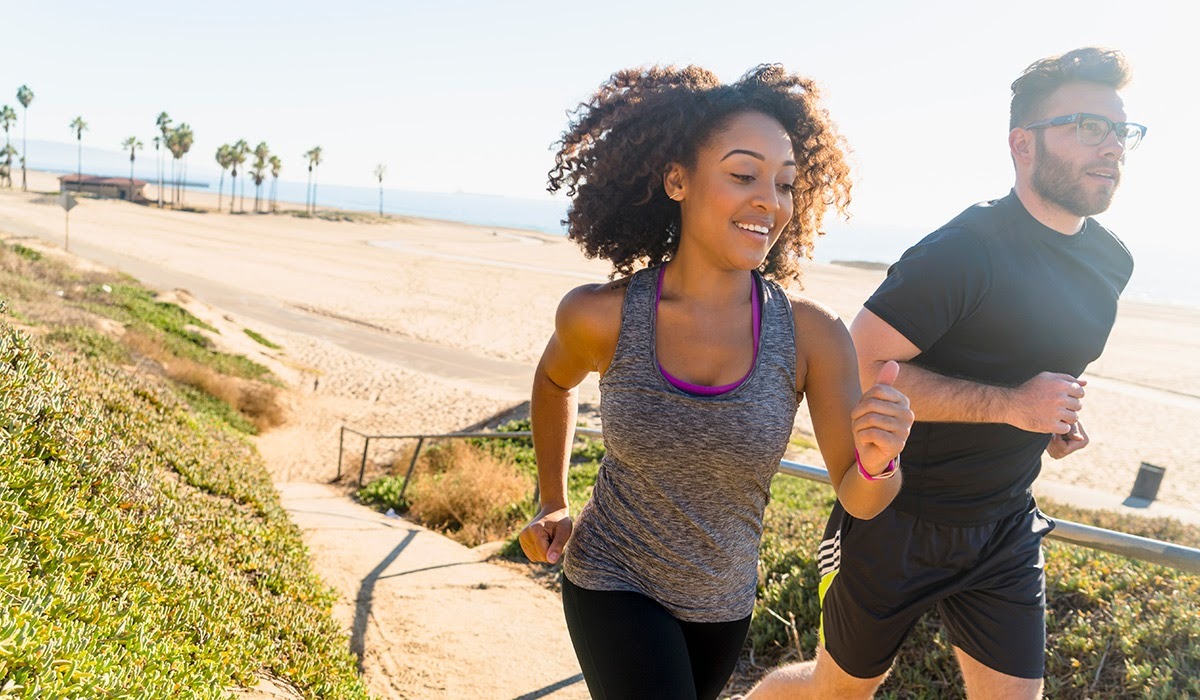 Young couple jogging on the beach for summer exercise plan workout