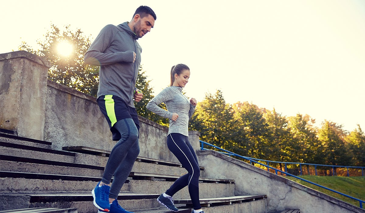 Young couple jogging down stairs, wearing cold weather workout clothes