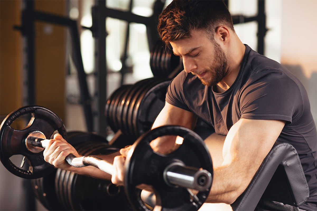 Young caucasian man lifting heavy weights to gain muscle mass